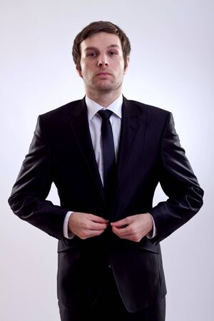 picture of a young business man buttoning his coat photo