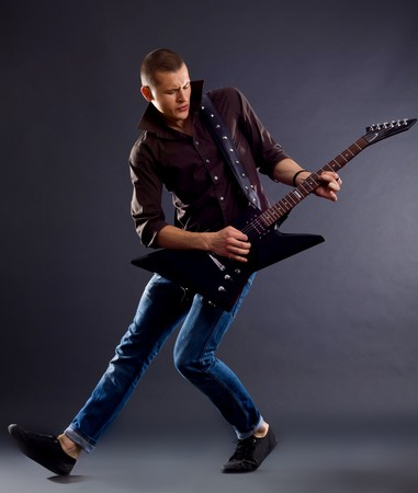 awesomen guitar player with an electric guitar on a dark background photo