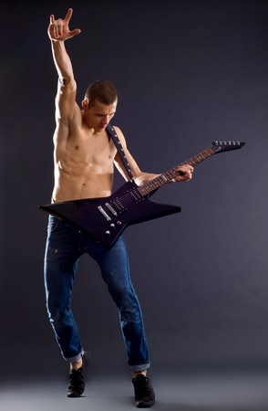 portrait of young man with guitar on dark background , wearing no top and making a rock and roll hand gesture photo