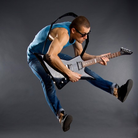 Awesome guitar player jumps with passion in studio Stock Photo - 7574527