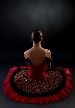 ballerina costume: back picture of a seated ballerina on dark background