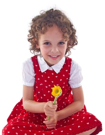 stitting: little girl wearing red dress is stitting with a flower in her hand Stock Photo