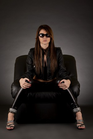 legs open: glamour girl with sunglasses sitting in  leather  chair on white