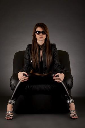 gambe aperte: Glamour ragazza con gli occhiali da sole seduti in poltrona in pelle su bianco