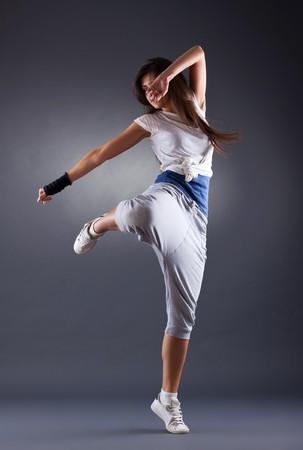 dance background: young female dancing jazz modern dance on a dark background