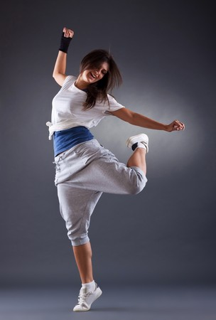 hiphop: young female dancing on the grey background
