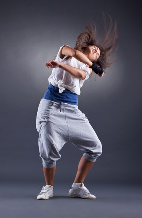 a young nice girl dancing modern dances over dark background photo