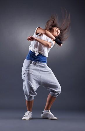 headbanging: a young nice girl dancing modern dances over dark background