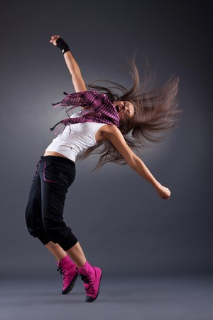 modern style dancer posing on studio background - energy pose with hair flying photo
