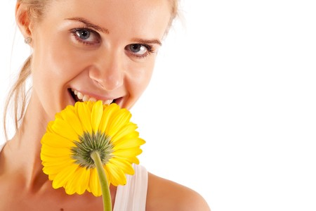 closeup of a pretty young woman smelling a yellow flower  photo