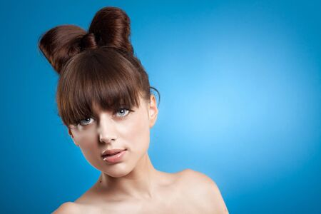 Beautiful young woman close-up portrait over blue background photo