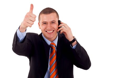 Happy business man showing thumb up while talking on the phone  photo