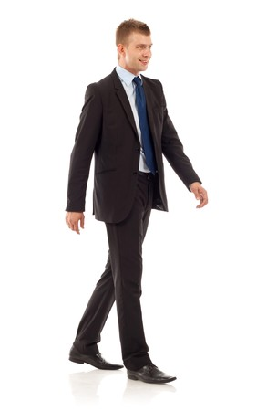 midlife: A young businessman is walking. He is smiling and looking away from the camera. isolated over white background