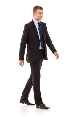 personas caminando: Un joven empresario es caminar. Est� sonriendo y mirando a la c�mara. aislados sobre fondo blanco