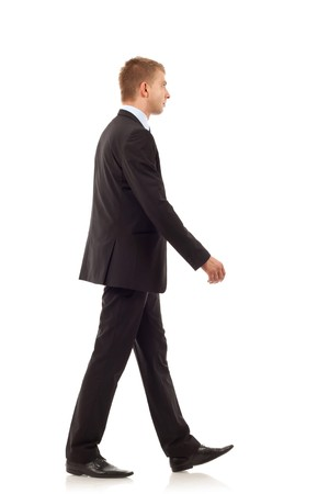 walking: Portrait of a happy young business man walking on white background