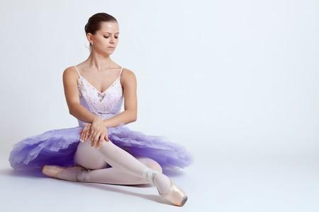 ballerina wearing a purple tutu sitting in studio photo