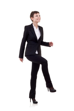 Young attractive business woman stepping on imaginary step  Stock Photo - 8041659