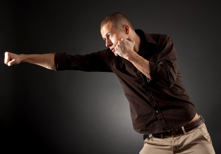 perspire: a man in fight action , wearing a shirt over dark background