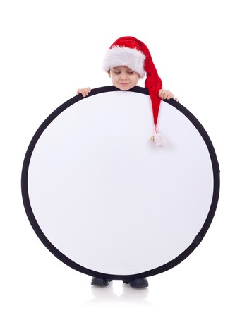 Child in a Christmas hat holding a round blank sign, over white photo