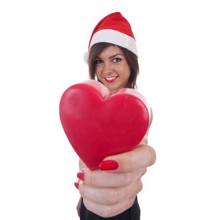 Cheerful woman in Santa hat holding a heart over white photo