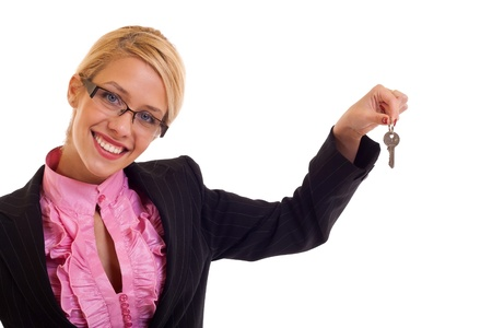 Smiling business woman holding keys in her left hand, isolated photo