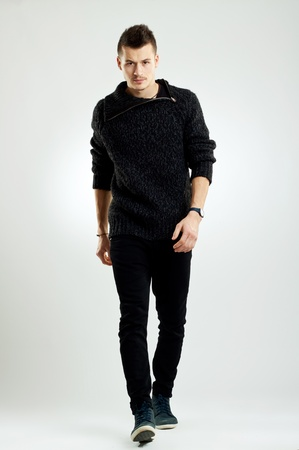 black sweater: picture of a male fashion model wearing wool sweater, walking  Stock Photo