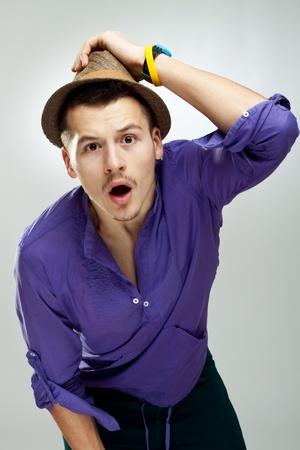 hombre con sombrero: hombre que llevaba un sombrero, studio disparo de moda de joven sorprendido Foto de archivo