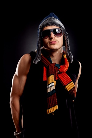 young fashion man in winter clothes and sunglasses, flexing his muscles photo