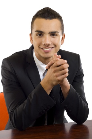 young business man in a black suit on a desk, isolated on white  photo
