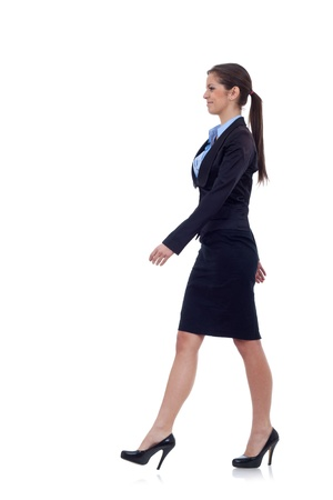 people isolated: young business woman is walking. She is smiling and looking away from the camera isolated over white background