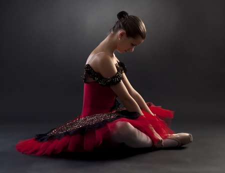 pointe: Beautiful ballerina wearing a red tutu on black background