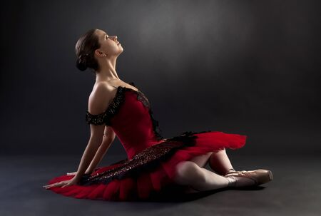 Beautiful ballerina sitting and looking up, over black photo