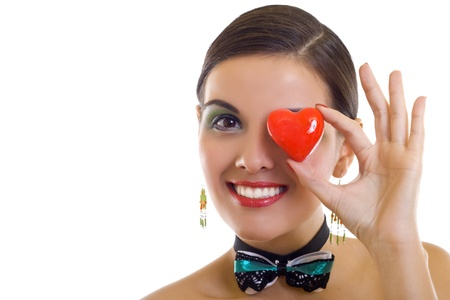 Beautiful woman holding red heart over one of her eyes photo