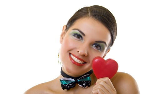 Cute young woman holds a heart symbol to her face  photo