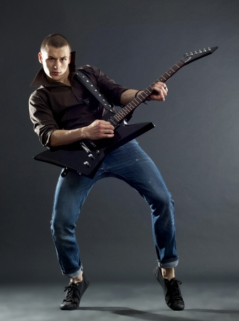 rock star: Passionate guitar player isolated against dark background  Stock Photo