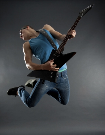 rock   roll: passionate guitarist jumps in the air over black