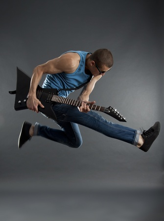 rock star jumping and playing an electric guitar photo