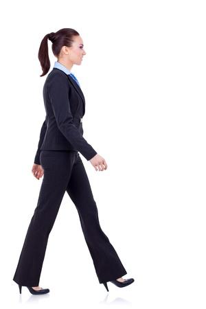 junge Business-Frau ist Fuß. Sie ist lächelnd und suchen Weg von der Kamera isolated over white background  Standard-Bild