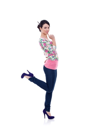 Young beautiful slim girl in stylish casual clothes looking at he camera with dreamy expression and hopping on one leg over white background Stock Photo