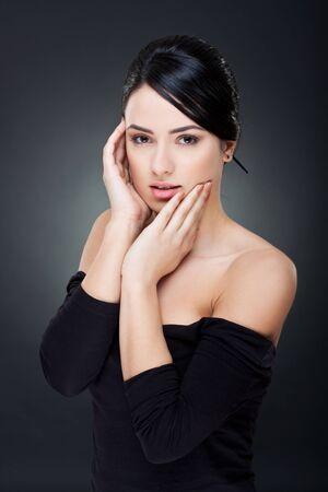 caras felices: Closeup retrato de una joven feliz con su rostro en manos sobre fondo oscuro