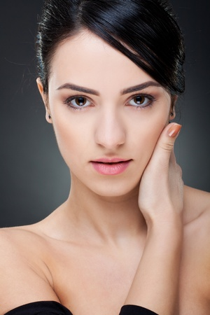 Portrait of a sexy young girl touching her face with hand against white background