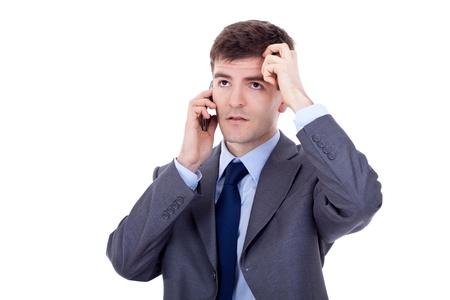 empresario enojado: hombre de negocios en un traje negro y un tel�fono m�vil con dolor de cabeza aislado en blanco Foto de archivo
