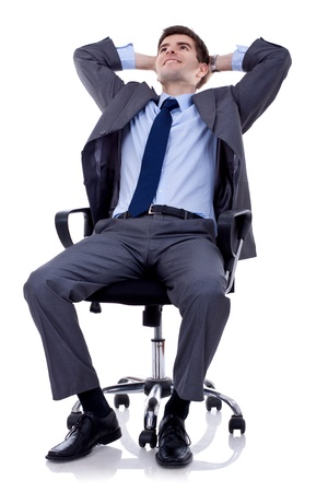 the stool: relaxed and dreaming business man sits on office chair over white background  Stock Photo