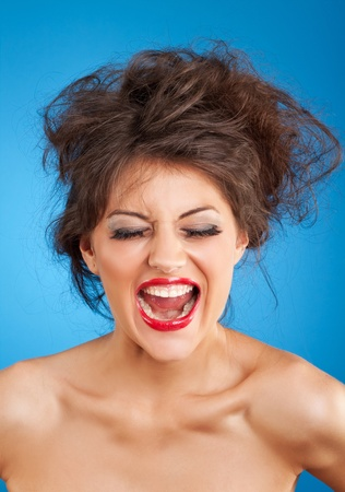 Portrait of screaming female with crazy hairstyle and red lips isolated on blue background  photo
