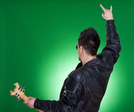 showbusiness: view from behind on the man with guitar making a rock gesture, over green background  Stock Photo