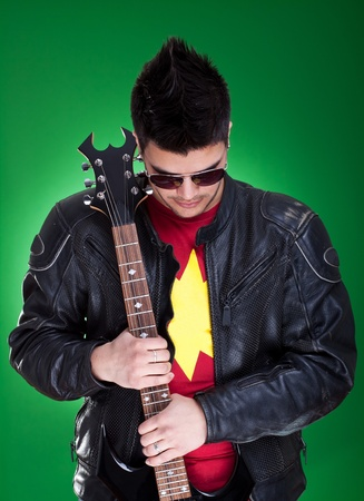 guitarist in black leather jacket and sunglasses thinking over green background photo
