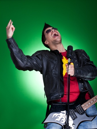 young guitarist screaming in the microphone and making a rock and roll gesture Stock Photo - 9153708