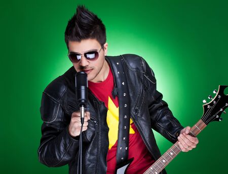 Young guitarist performing rock and roll music, over green background photo
