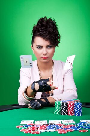 serious brunette in casino throwing a pair of aces on the table photo