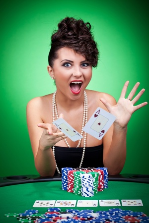 Young woman with aces four of a kind playing poker and throwing the cards in the excitement Stock Photo - 9153715
